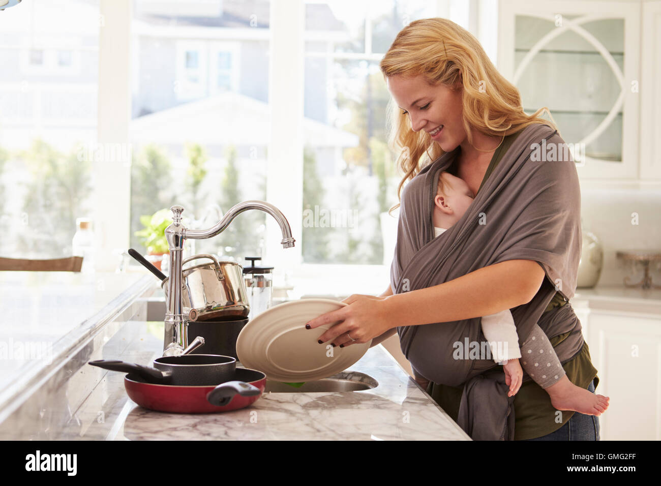 Busy Mother With Baby In Sling Multitasking At Home - Stock Image