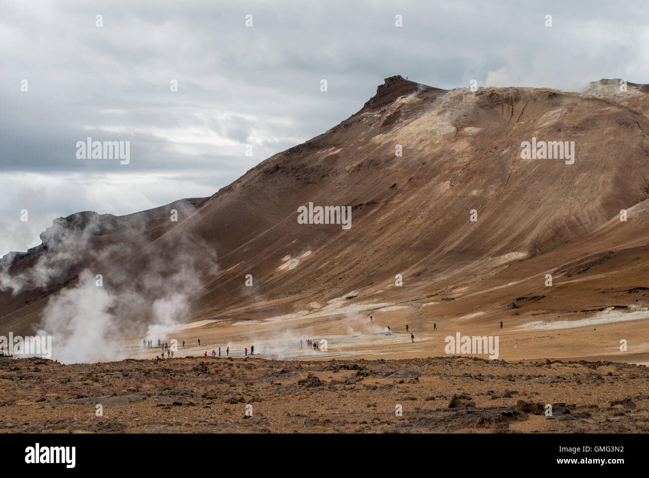 Unidentifiable tourists admire volcanic activity in Reykjahlid, Iceland - Stock Image