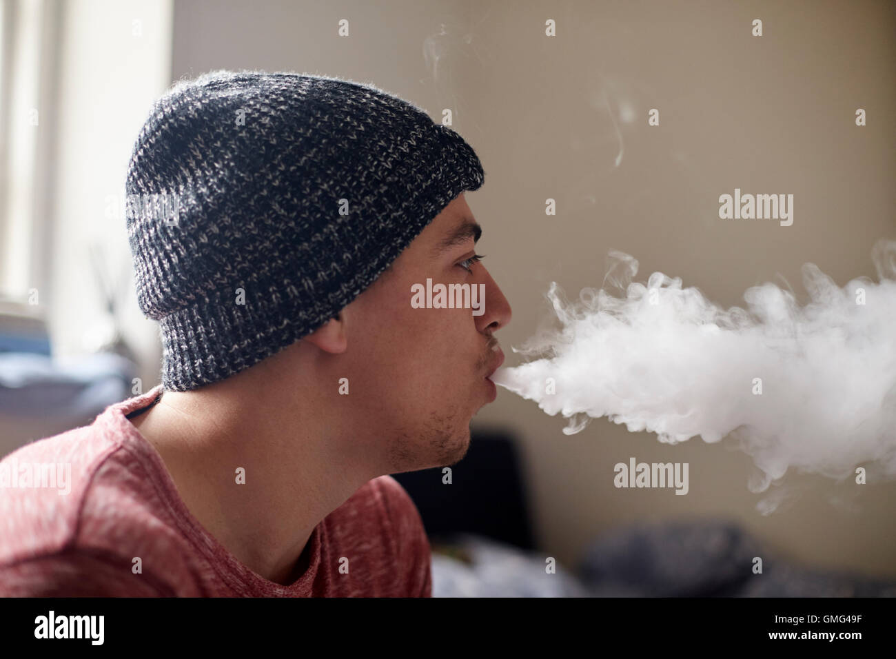 Young Man Exhaling Whilst Using Vapourizer - Stock Image