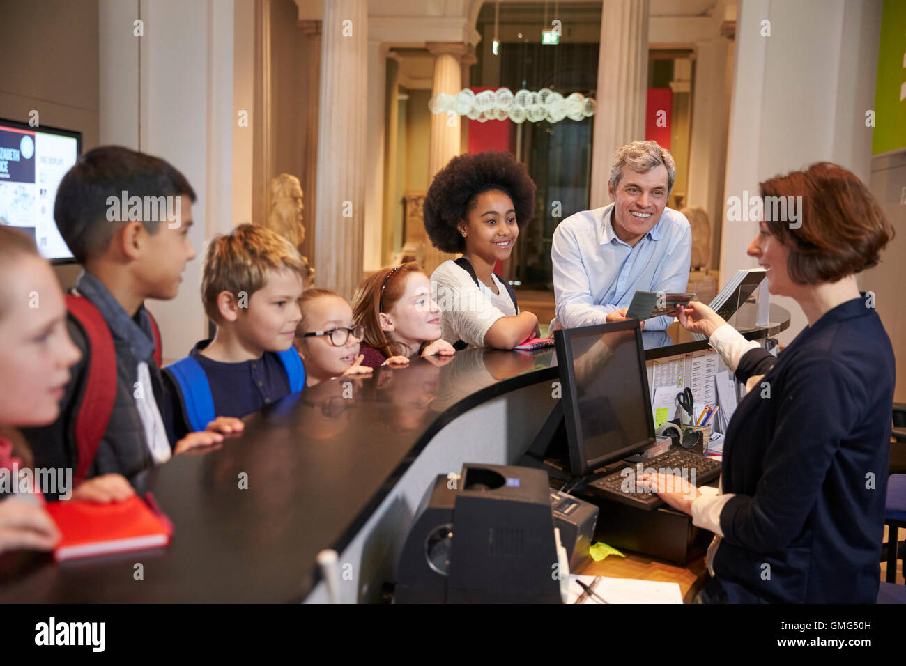 Class On School Trip Buying Entry Tickets To Museum - Stock Image