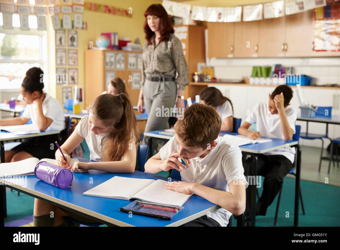 Teacher walking in her busy primary school classroom - Stock Image