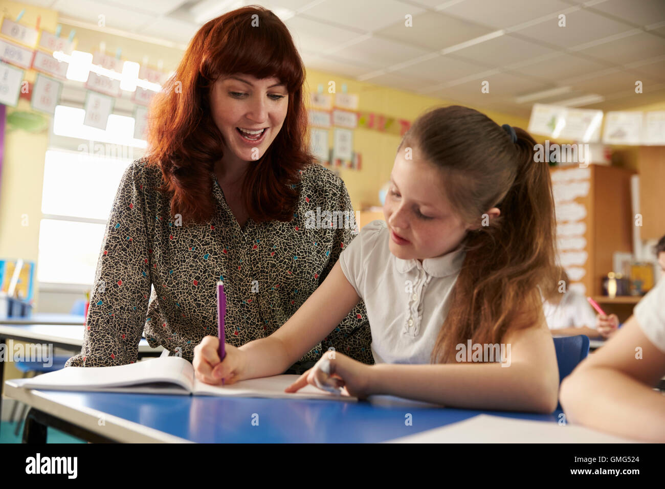 Primary school teacher helping with classwork at girl's desk - Stock Image