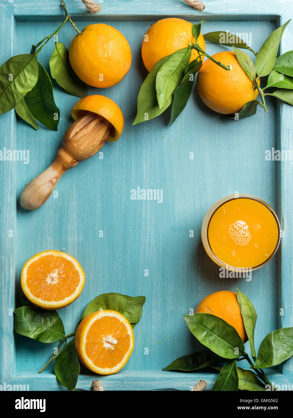Fresh orange juice in glass and oranges with leaves on wooden turquoise blue painted background - Stock Image