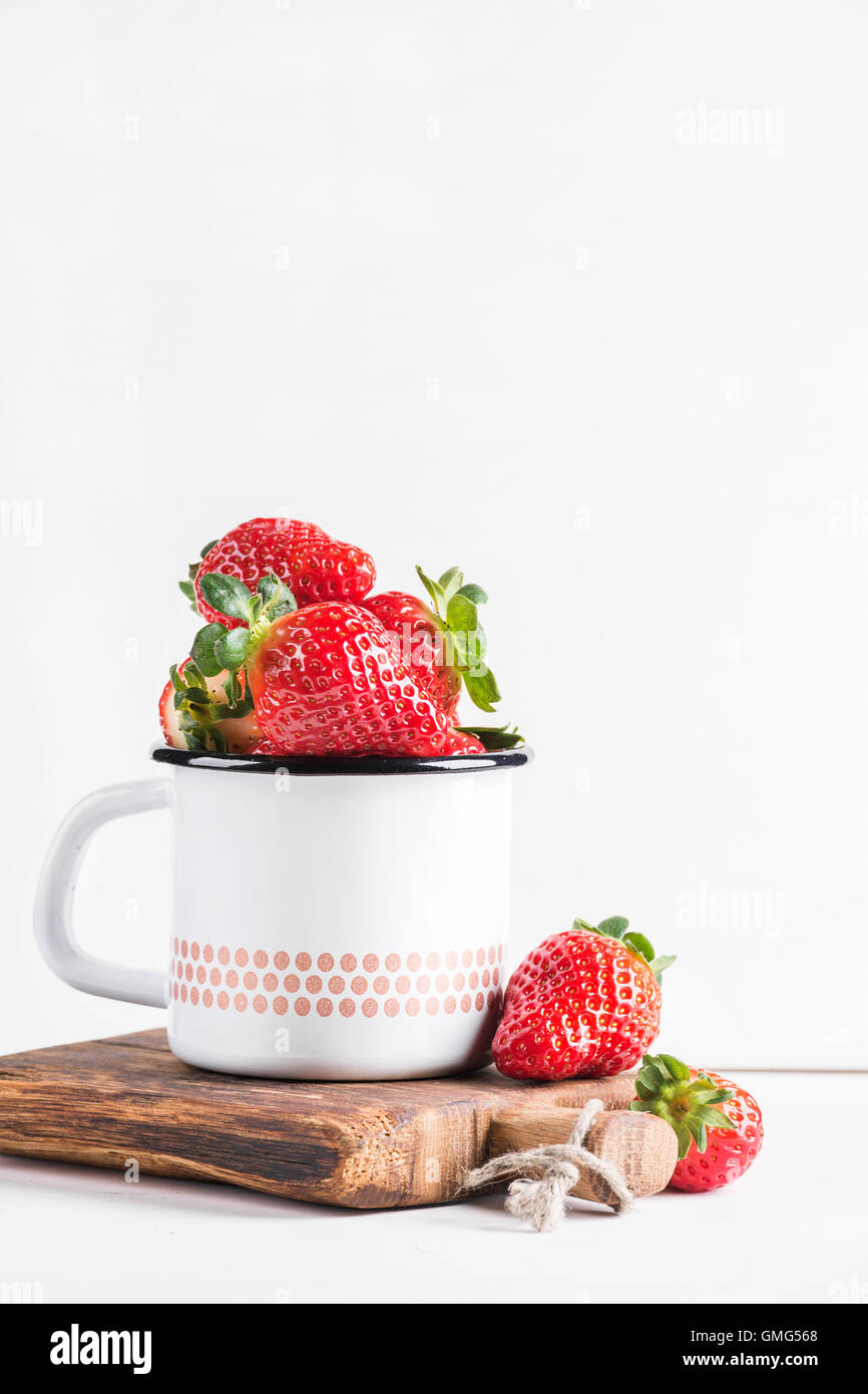 Fresh ripe red strawberries in country style enamel mug on rustic wooden board over white background Stock Photo
