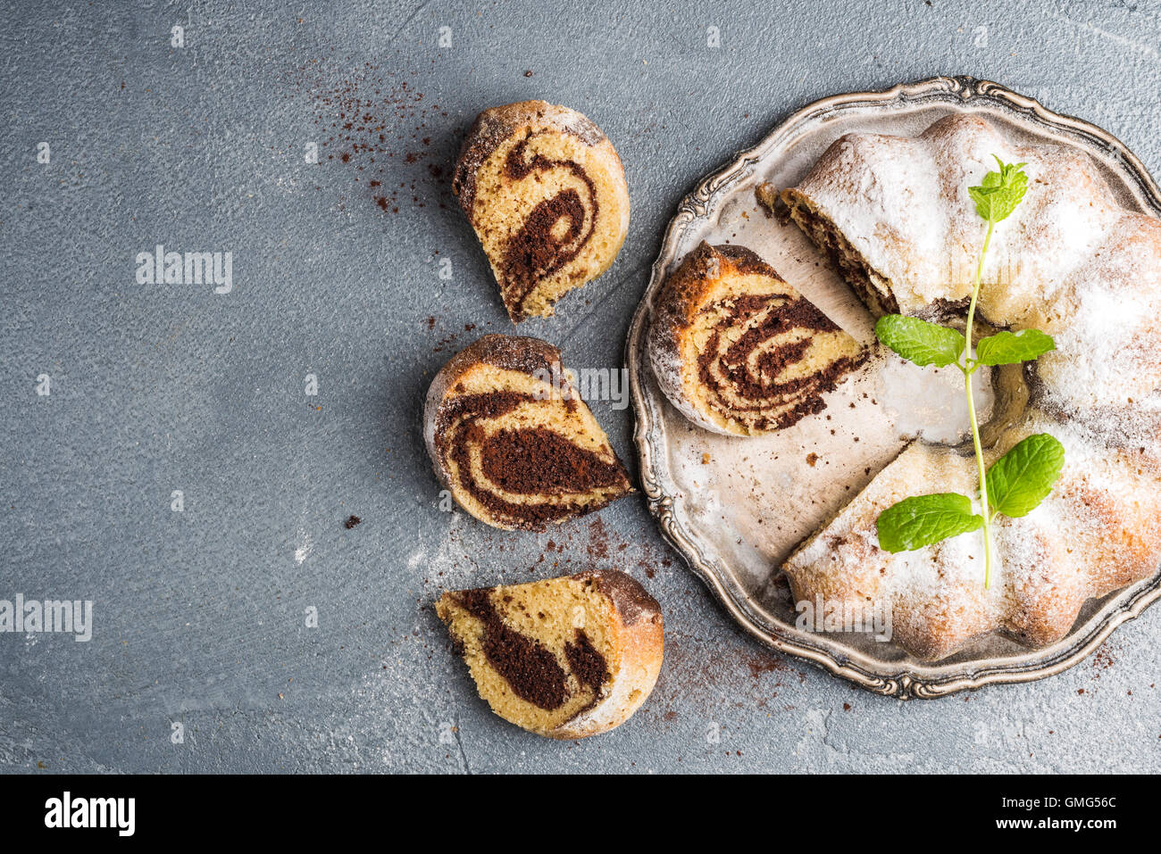 Zebra bundt cake cut into pieces and mint leaves - Stock Image