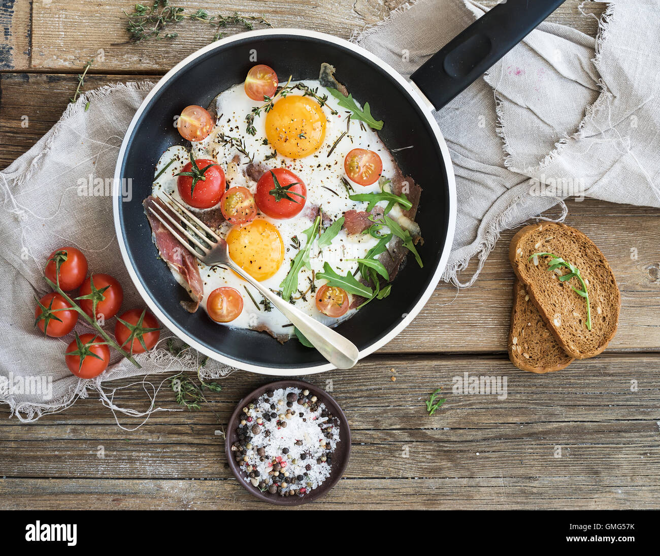Pan of fried eggs, bacon and cherry-tomatoes with bread - Stock Image