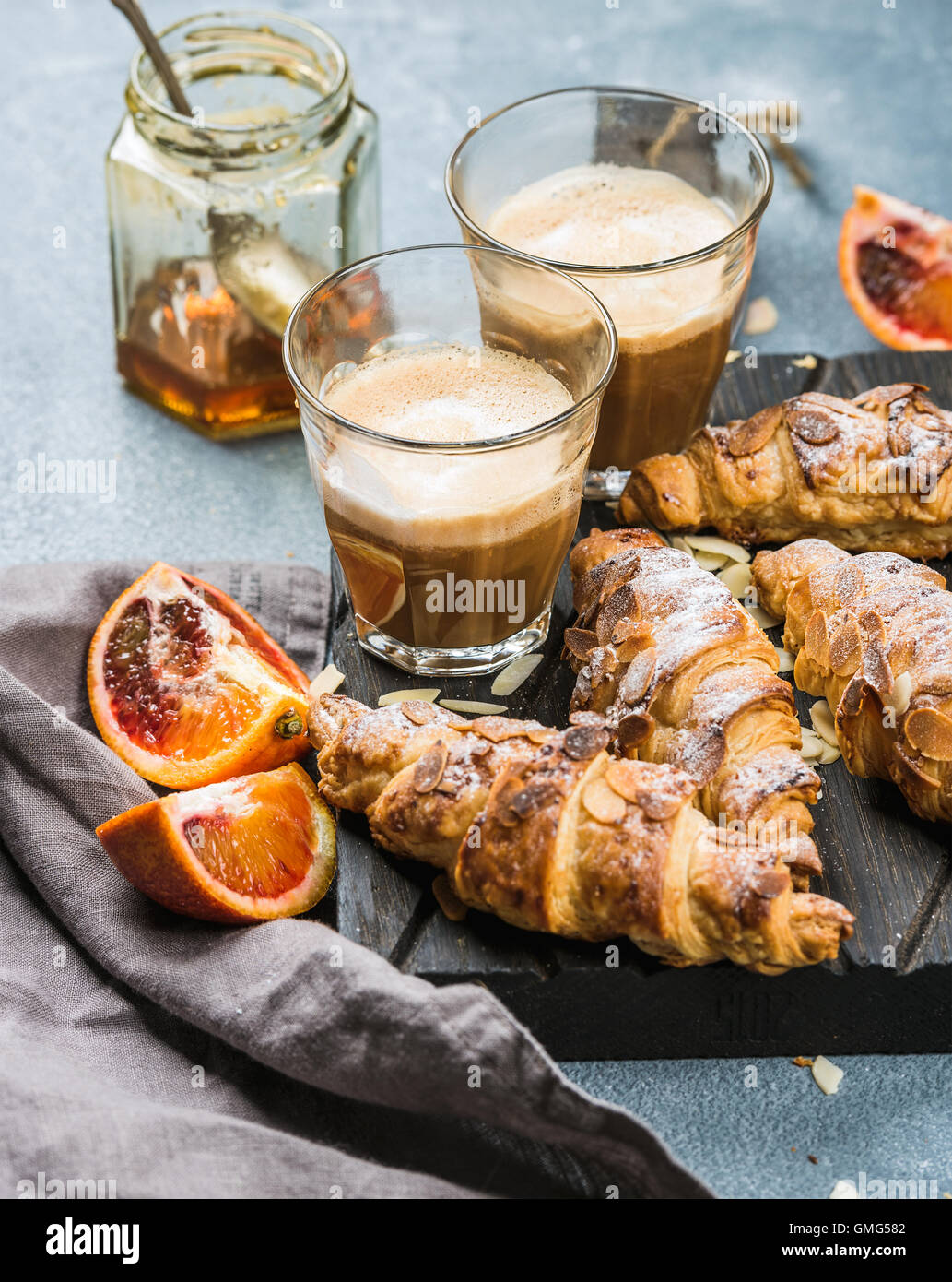 Traditional Italian style home breakfast. Latte in glasses, almond croissants and red bloody Sicilian oranges over - Stock Image