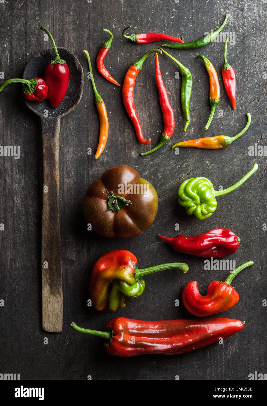 Red and green vegetables with rustic old spoon on dark wooden background, top view - Stock Image