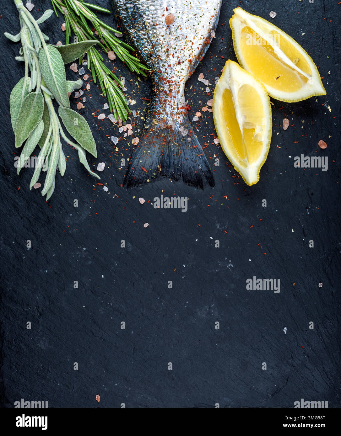 Tail of fresh raw Dorado or sea bream fish on black slate stone board with spices, herbs, lemon and salt - Stock Image
