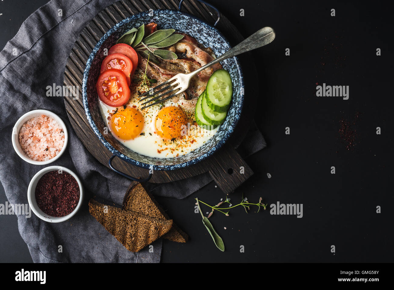 Breakfast set. Pan of fried eggs with bacon, fresh tomato, cucumber, sage and bread on dark serving board over black - Stock Image