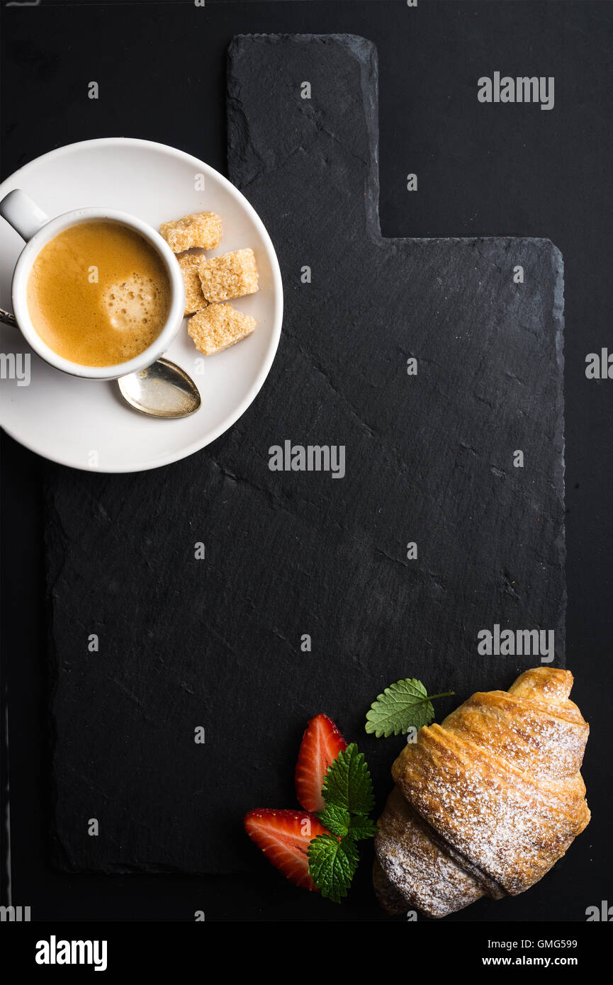 Espresso coffee cup and croissant with fresh strawberries on black  slate stone board over dark background - Stock Image