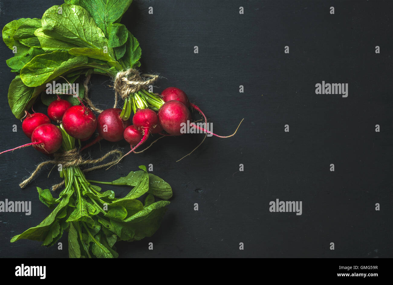 Bunch of radish with leaves on black background - Stock Image