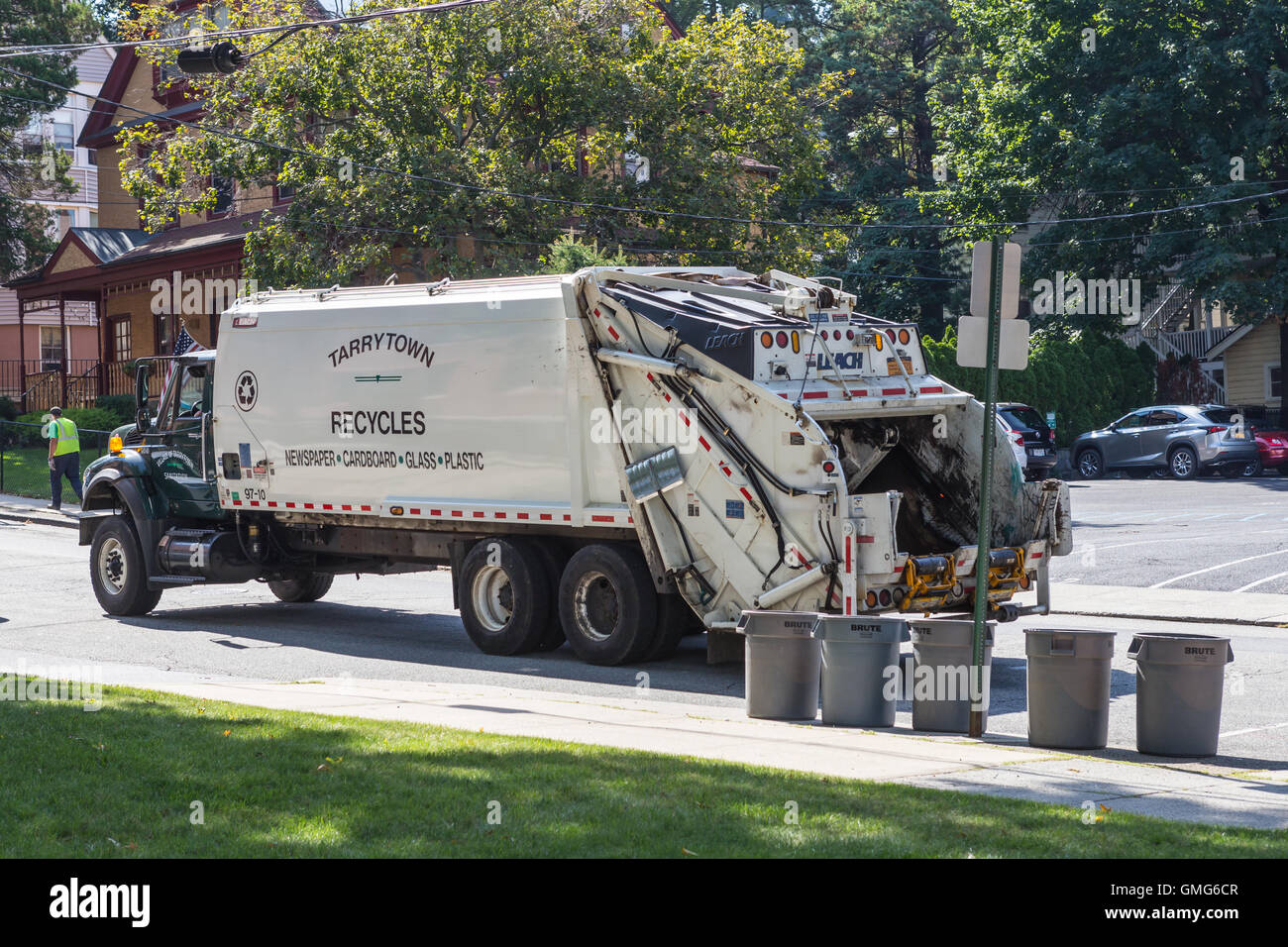 Sanitation workers collect recyclables using a rear-loading garbage truck on a street in Tarrytown, New York. - Stock Image
