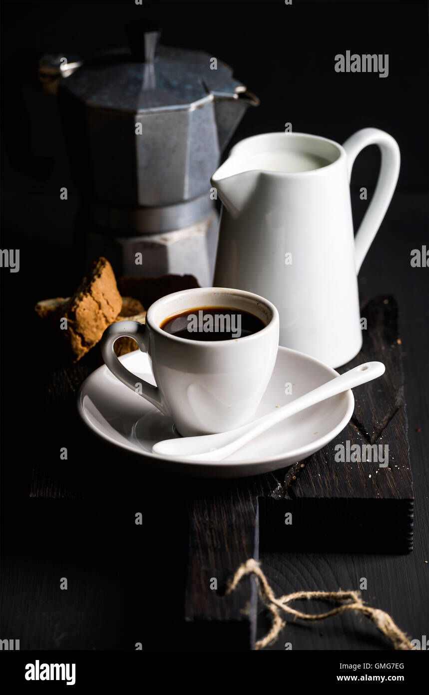 Cup of hot espresso, creamer with milk, cantucci and moka coffee pot on a rustic wooden board - Stock Image
