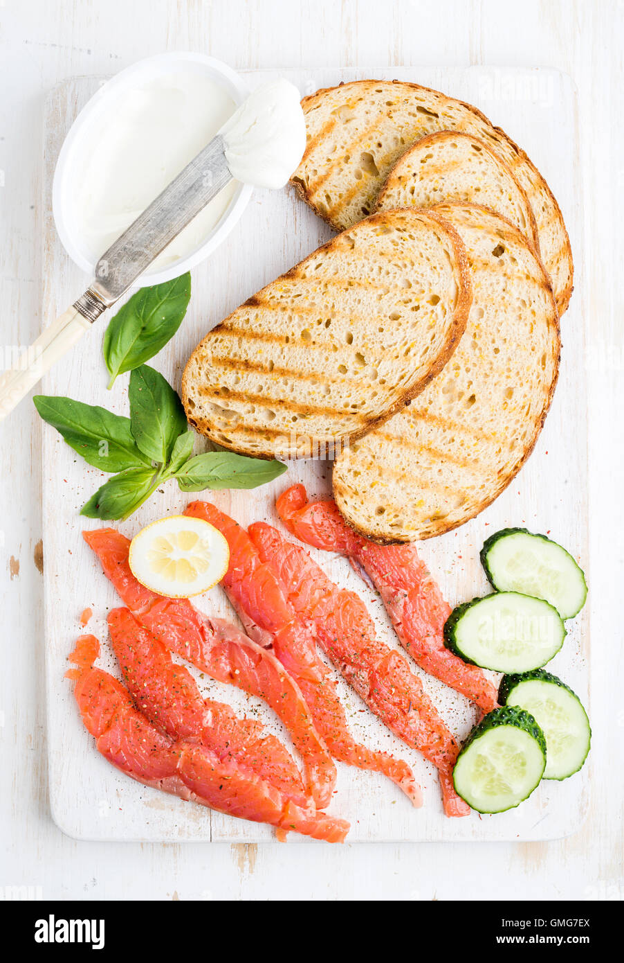 Ingredients for healthy sandwich. Grilled bread slices, smoked salmon, cottage cheese, cucumber nd basil on white - Stock Image