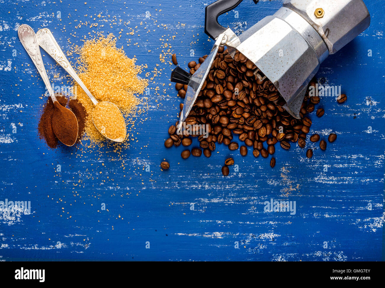 Arabika eans in moka pot,brown sugar and ground coffee on wooden blue painted table - Stock Image