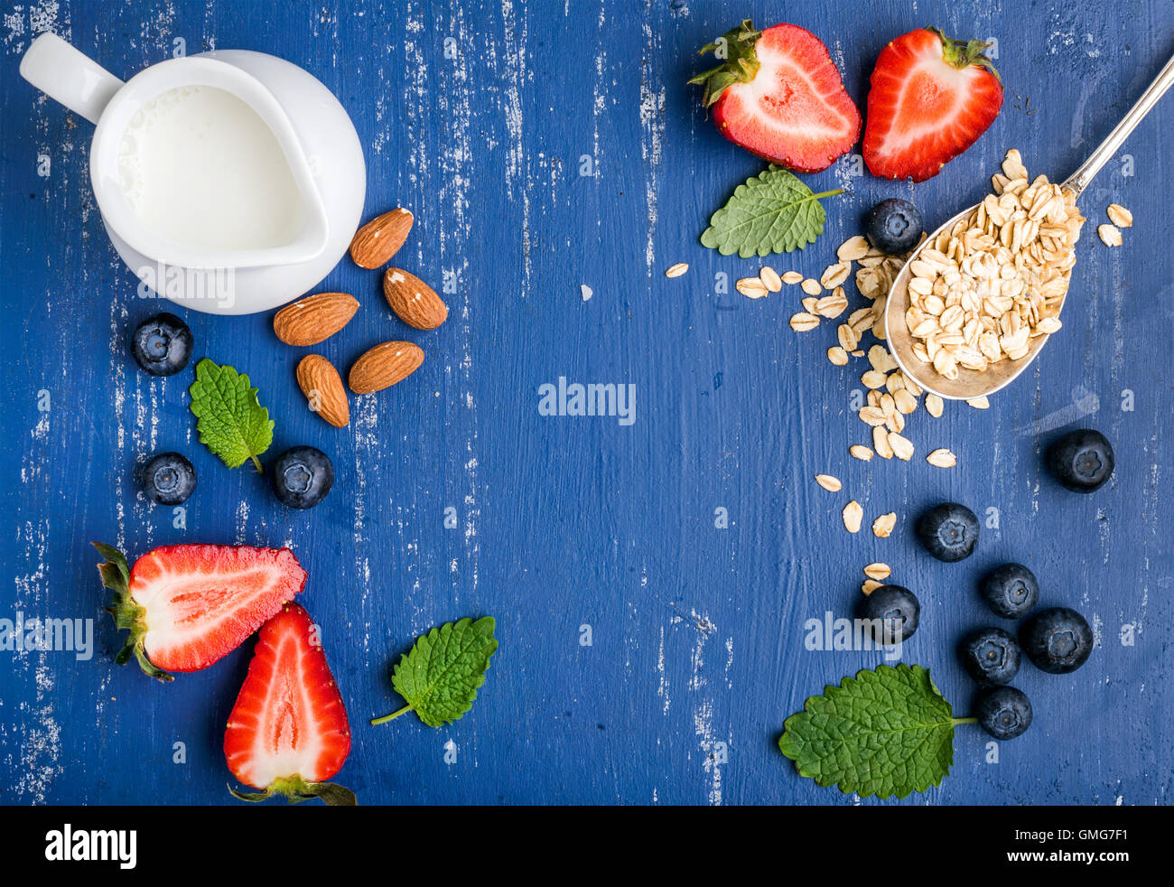 Healthy breakfast ingredients food frame. Oatmeal, milk in creamer, berries, almond and mint on painted blue wooden - Stock Image