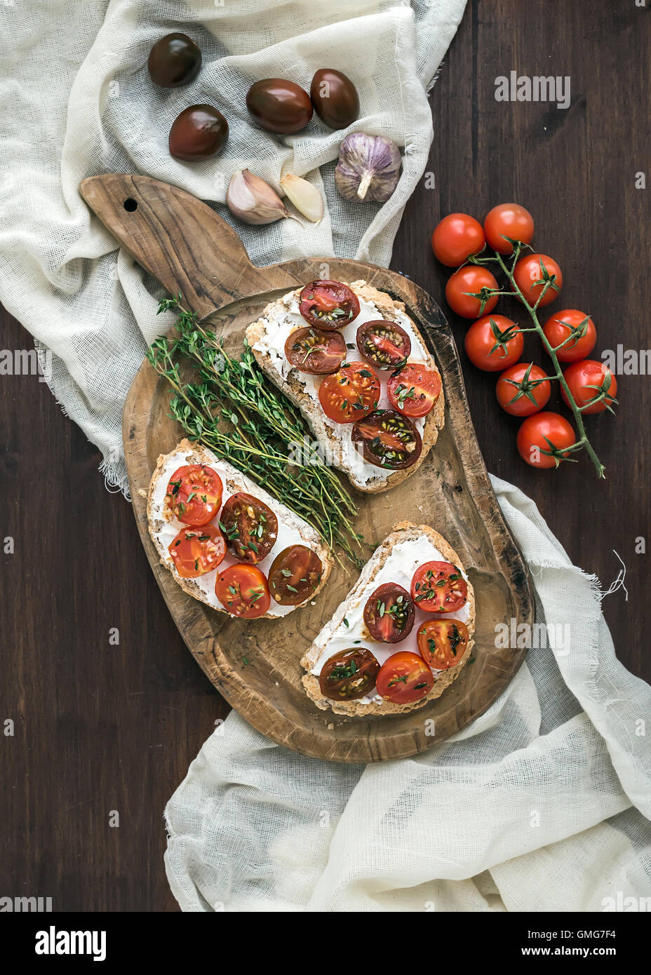 Sandwiches brushtta with roasted cherry tomatoes, soft cheese - Stock Image