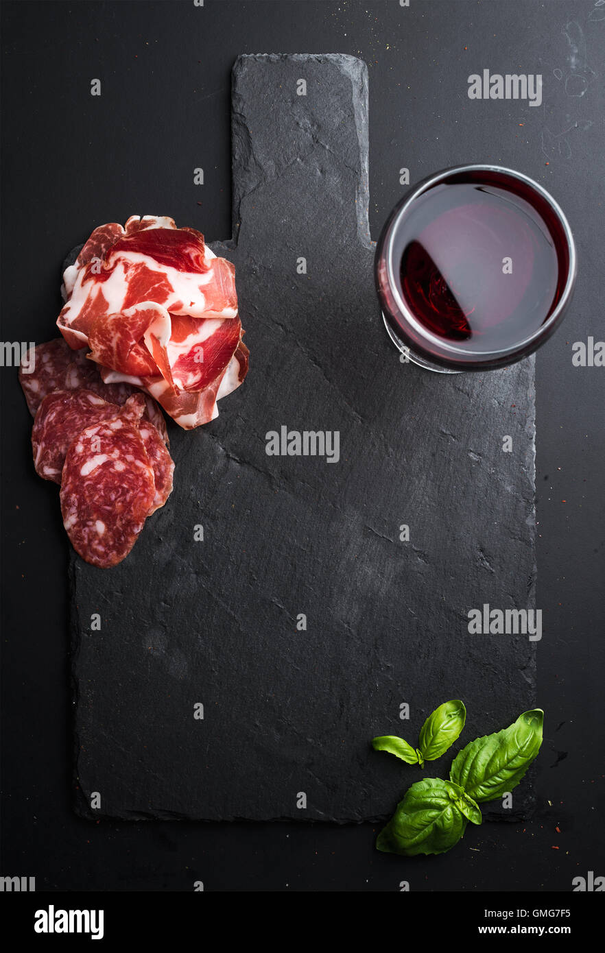 Glass of red wine, meat appetizer and basil on black  slate stone board over dark background - Stock Image