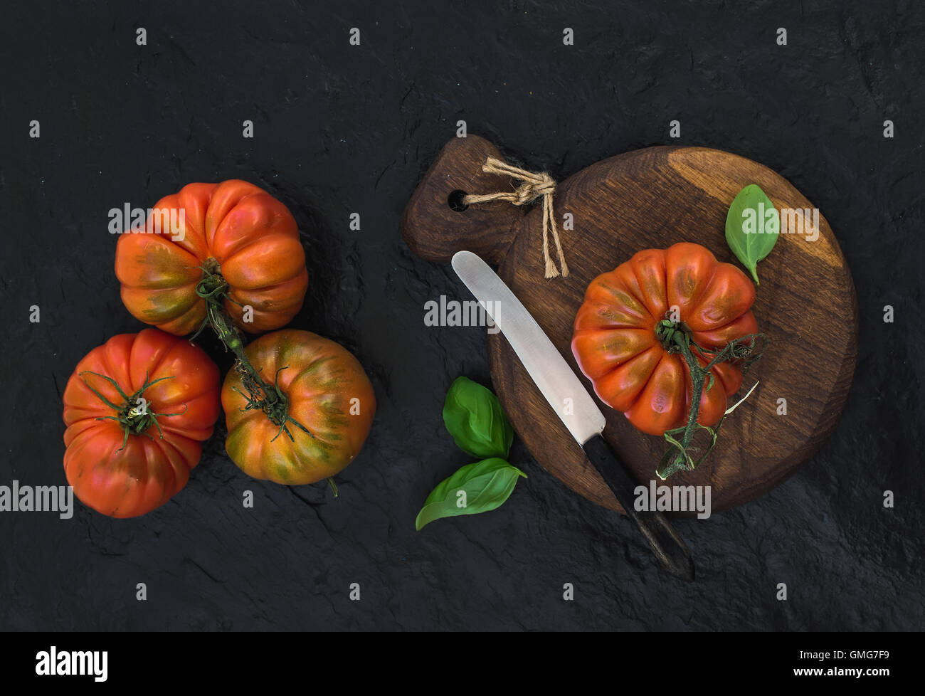 Fresh ripe hairloom tomatoes and basil leaves on rustic wooden board - Stock Image