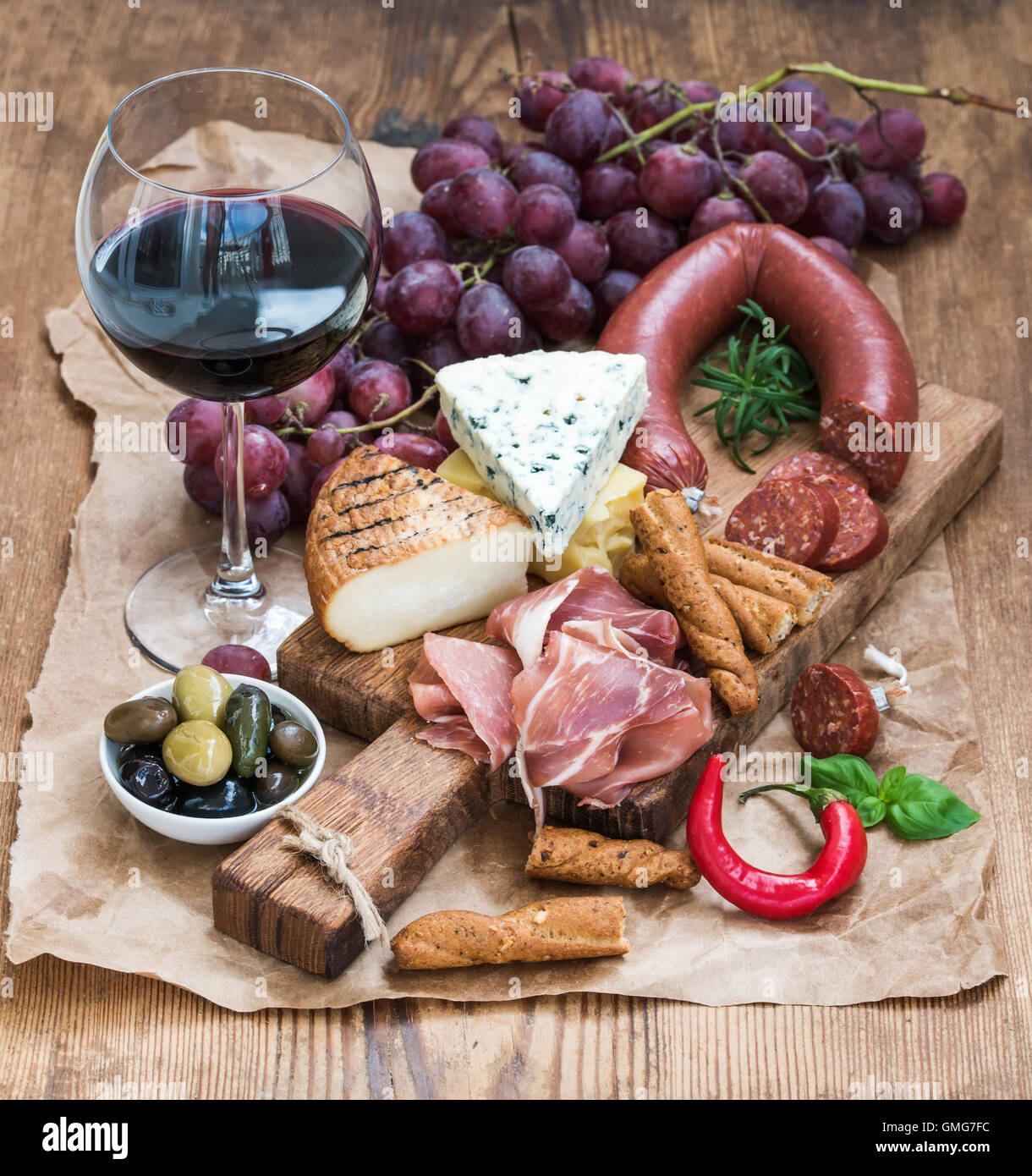 Glass of red wine, cheese and meat board, grapes,fig, strawberries, honey, bread sticks  on rustic wooden table, Stock Photo