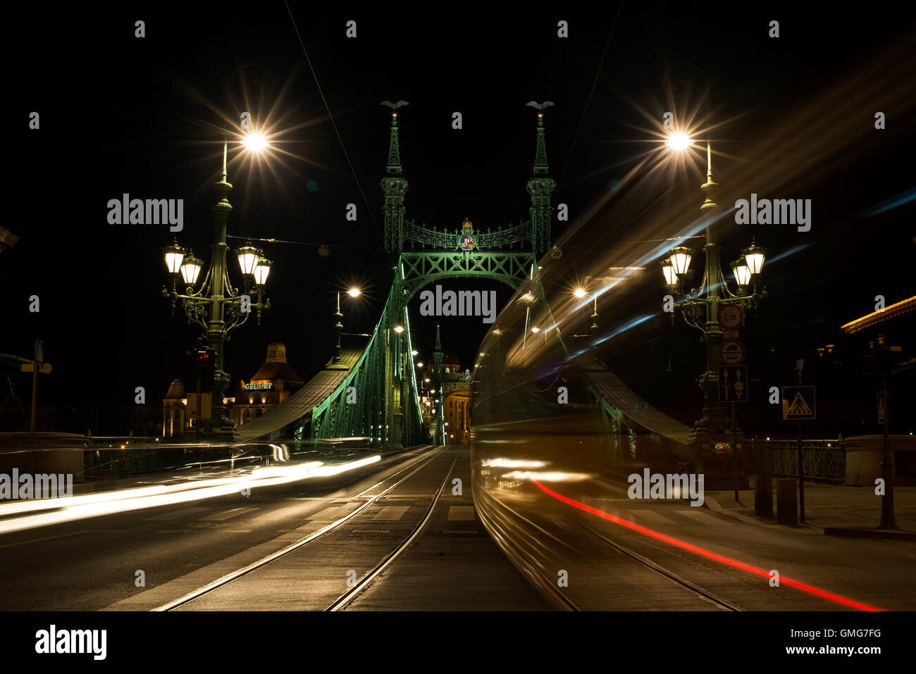 Night view of tram and cars crossing Liberty Bridge in Budapest, Hungary Stock Photo
