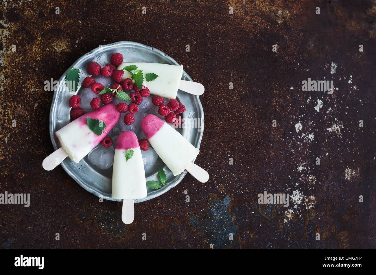 Raspberry lime yougurt ice-creams or popsicles with fresh berries and ice-cubeson - Stock Image