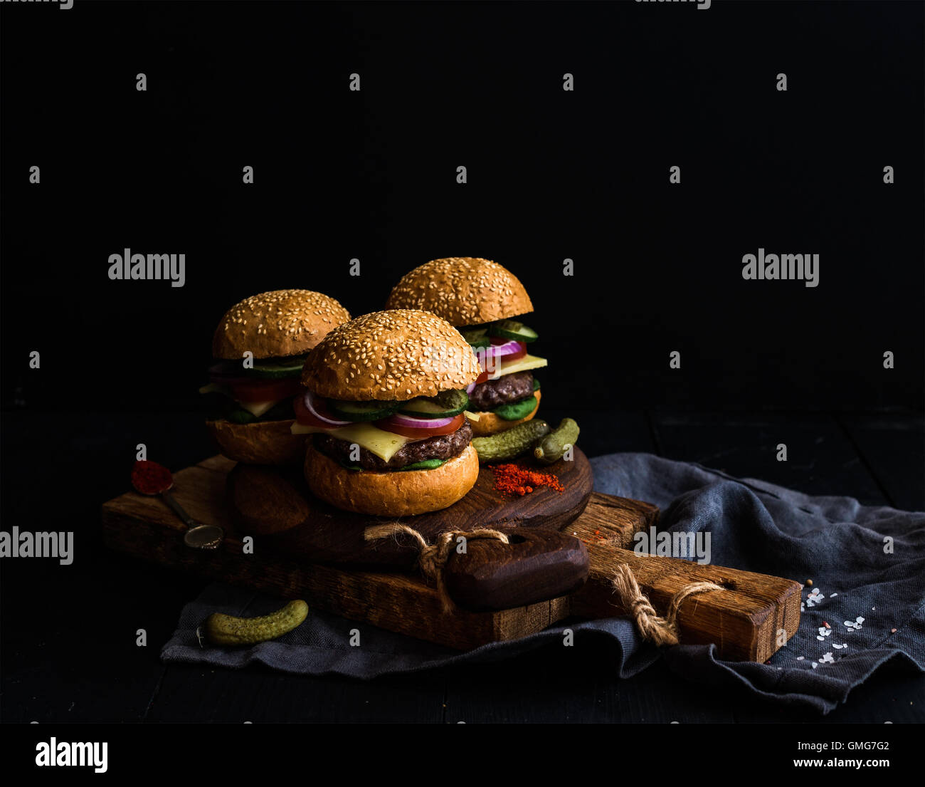 Fresh beef burgers with pickles and spices on rustic wooden boards, black background. - Stock Image