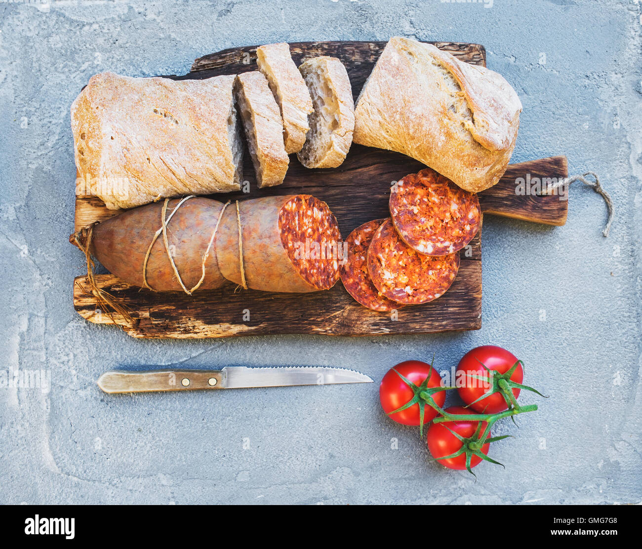 Wine snack set. Hungarian mangalica pork salami sausage, rustic bread and fresh tomatoes on dark wooden board over Stock Photo