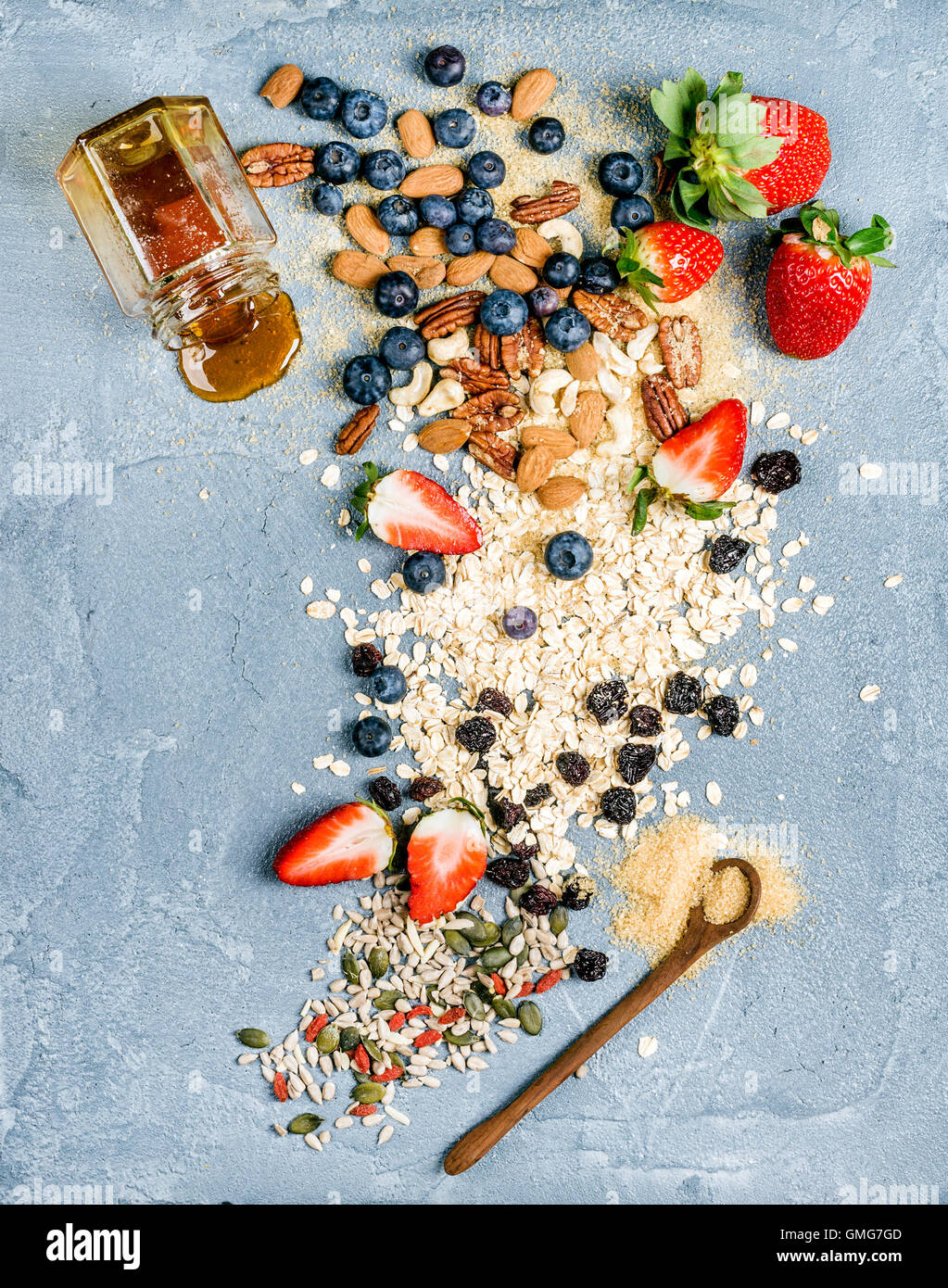 Ingredients for cooking healthy breakfast.  Strawberries, blueberries, nuts, oat flakes, dried fruits, honey with - Stock Image