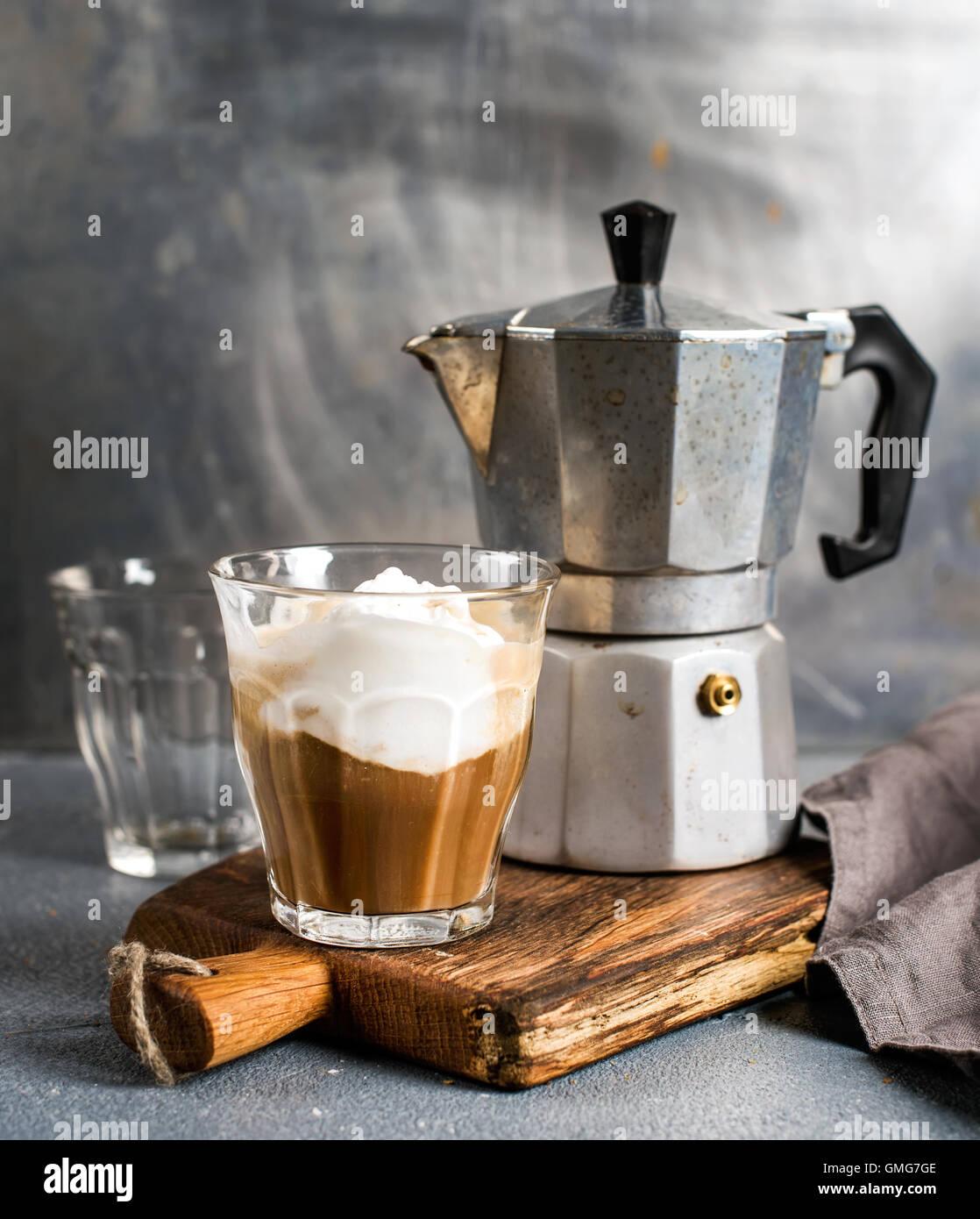 Glass of coffee with ice cream on rustic wooden board and steel Italian Moka pot - Stock Image