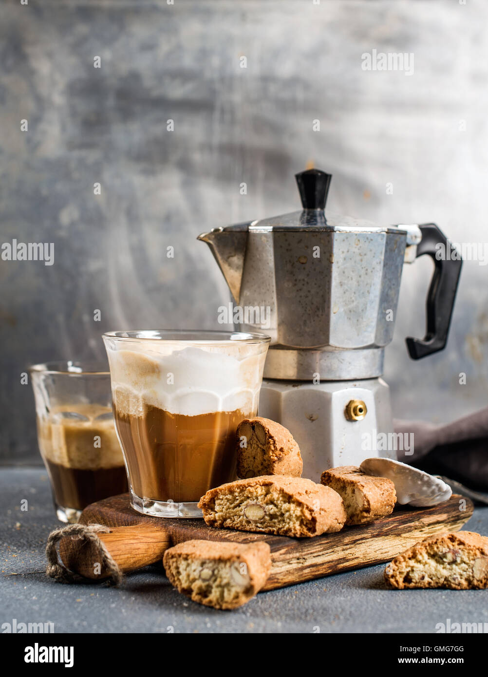 Glass of latte coffee on rustic wooden board, cantucci biscuits and steel Italian Moka pot, grey background - Stock Image