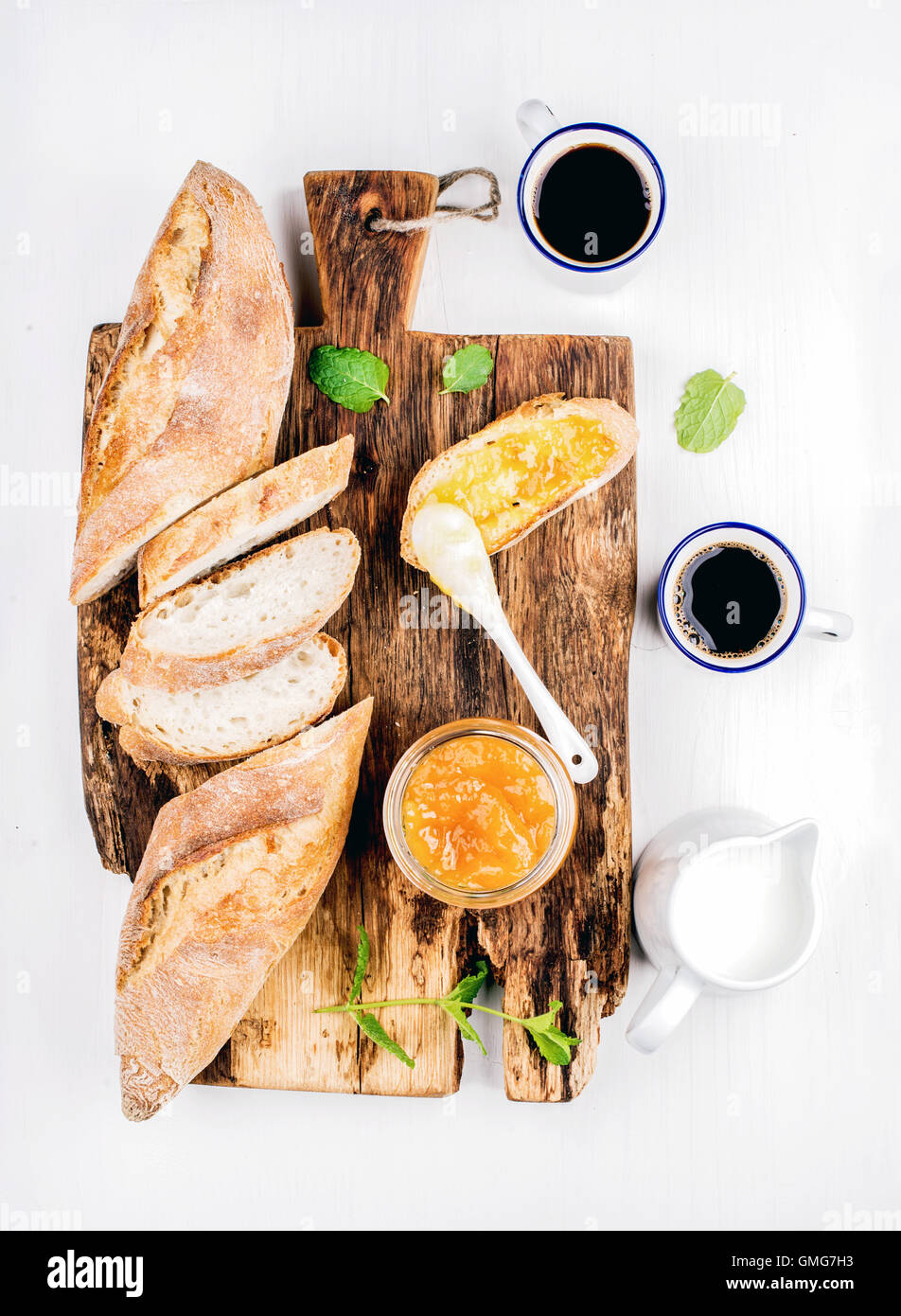 Breakfast set. Baguette, orange jam and coffee in cups on rustic wooden board over white painted background - Stock Image