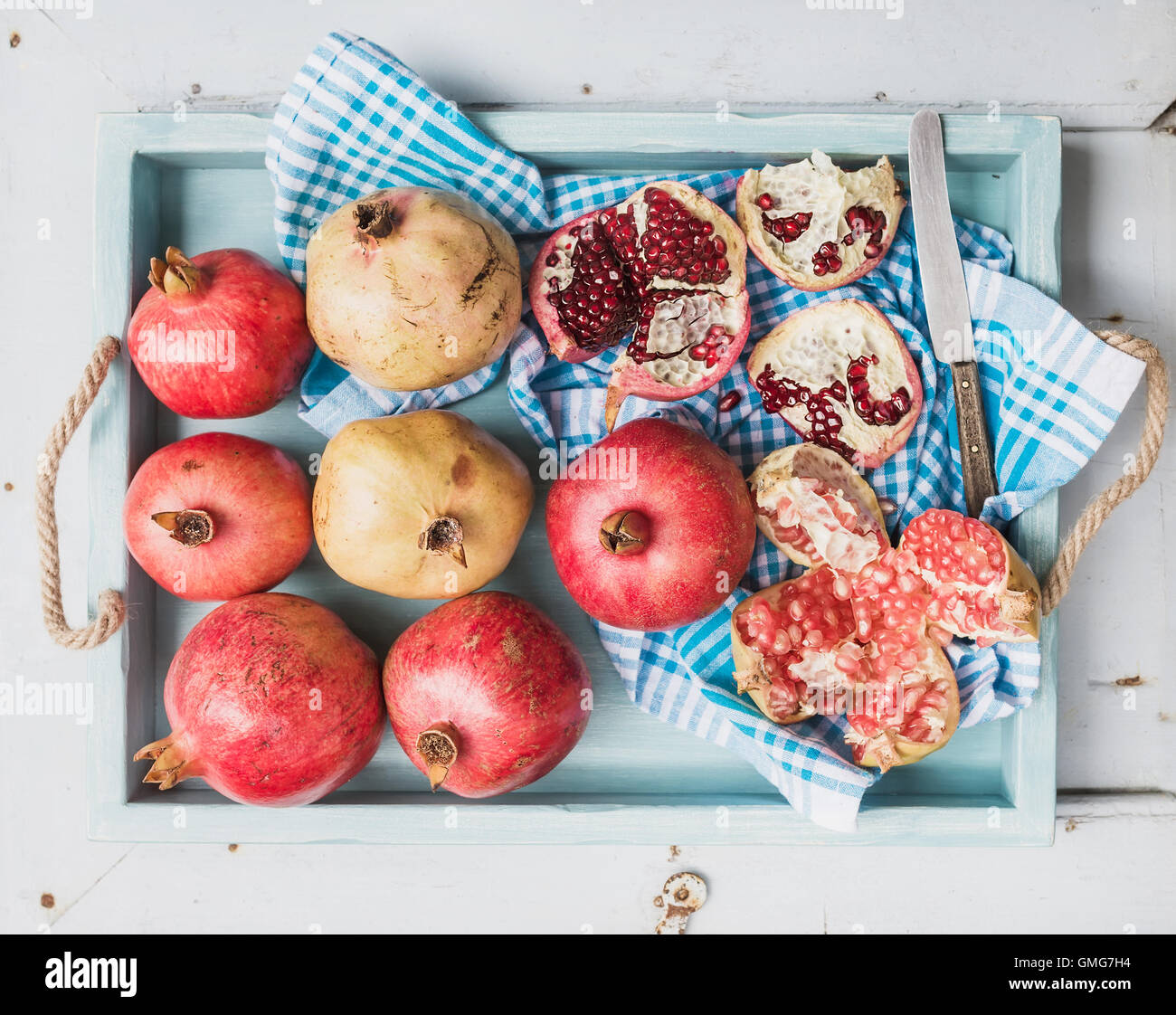 Red and white pomegranates with knife on kitchen towel in blue tray over light painted wooden backdrop - Stock Image