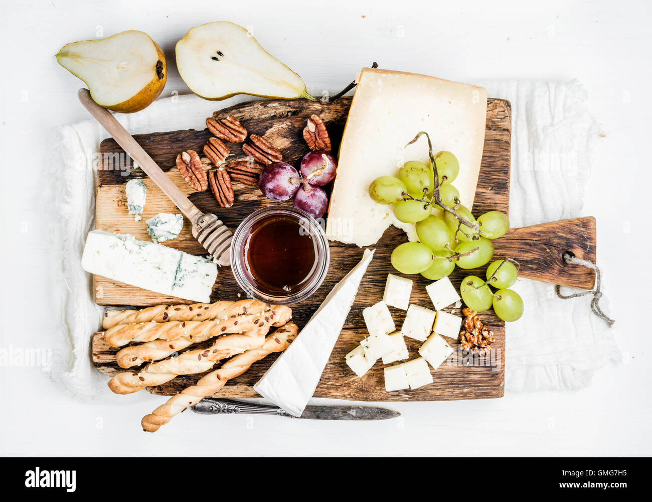 Cheese appetizer set. Various types of cheese, honey, grapes, pear, nuts and bread grissini sticks on rustic wooden Stock Photo