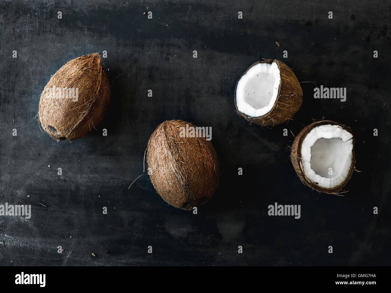 Whole and broken coconuts over dark grunge background - Stock Image