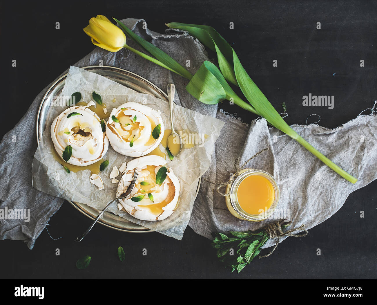 Merengues with lemon curd, fresh mint on silver tray, beige kitchen towel - Stock Image