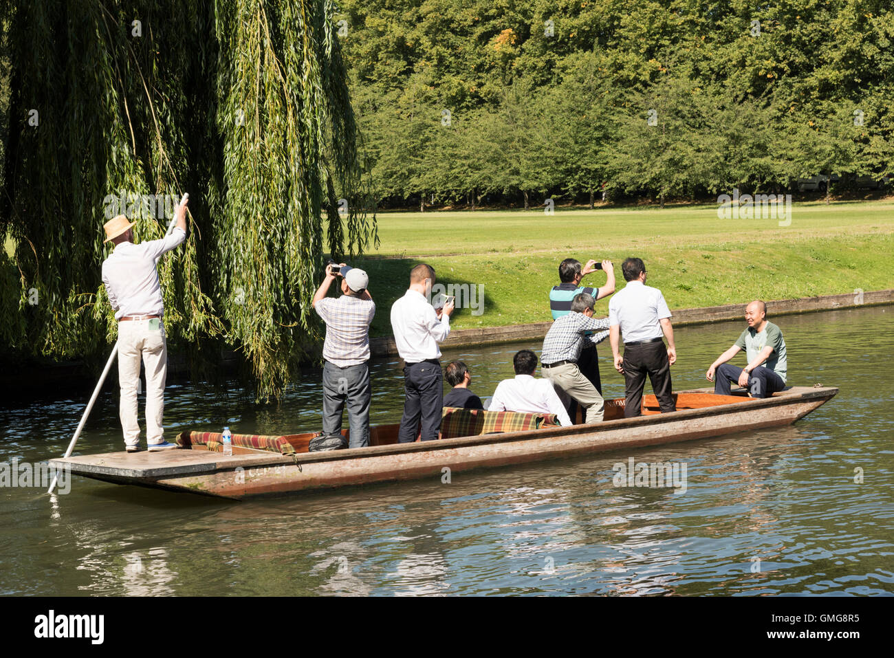 Tourists punting on the River Cam on the Backs at Cambridge Uk in summer standing up in the boat taking photographs - Stock Image