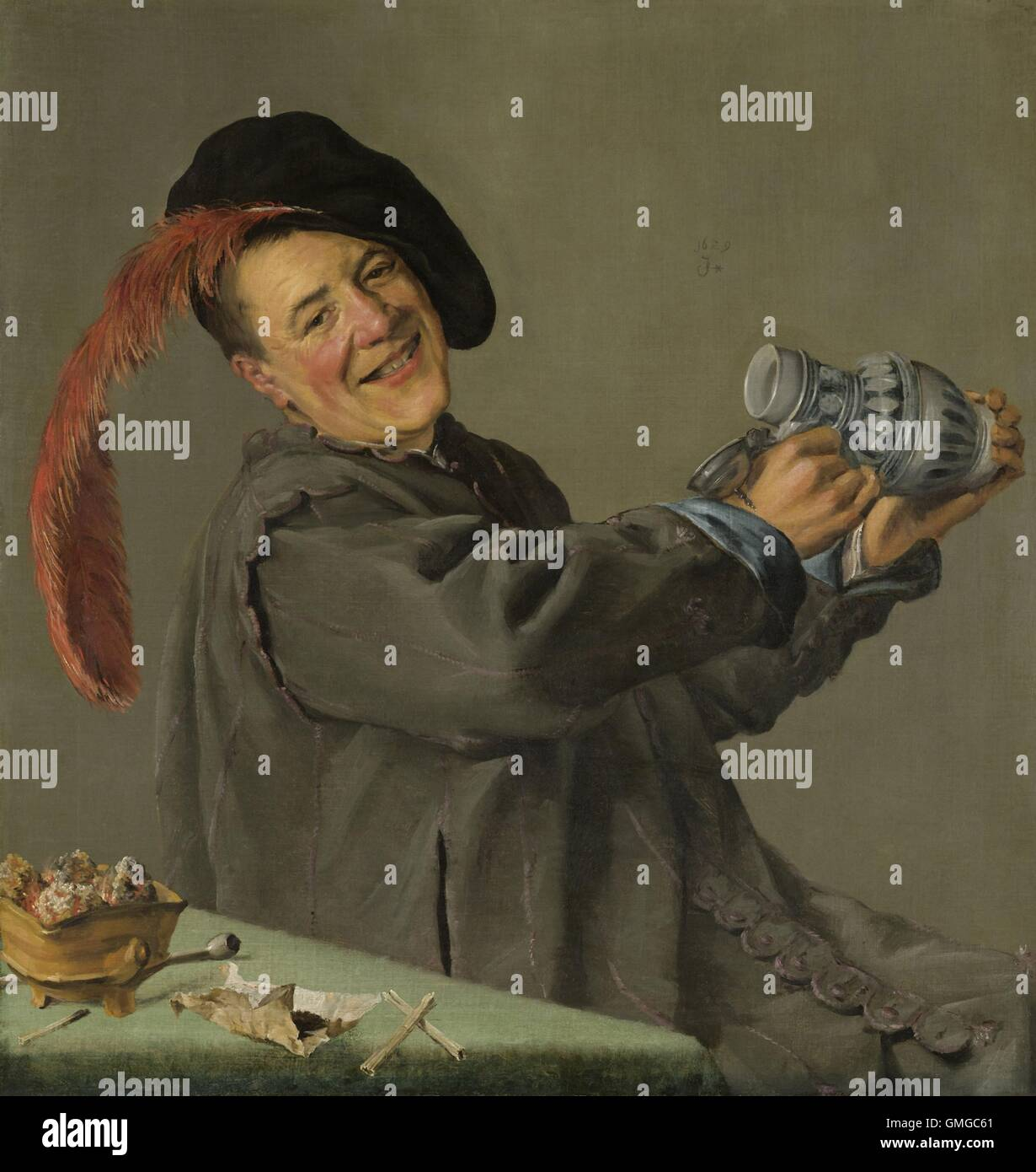 The Merry Drinker, by Judith Leyster, 1629, Dutch painting, oil on canvas. A smiling man raises his tankard, while - Stock Image