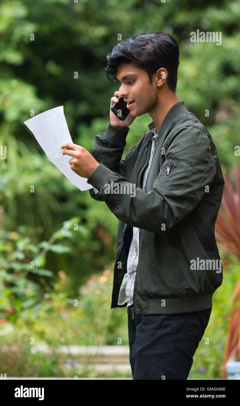 A male student with his GCSE results at a school. - Stock Image
