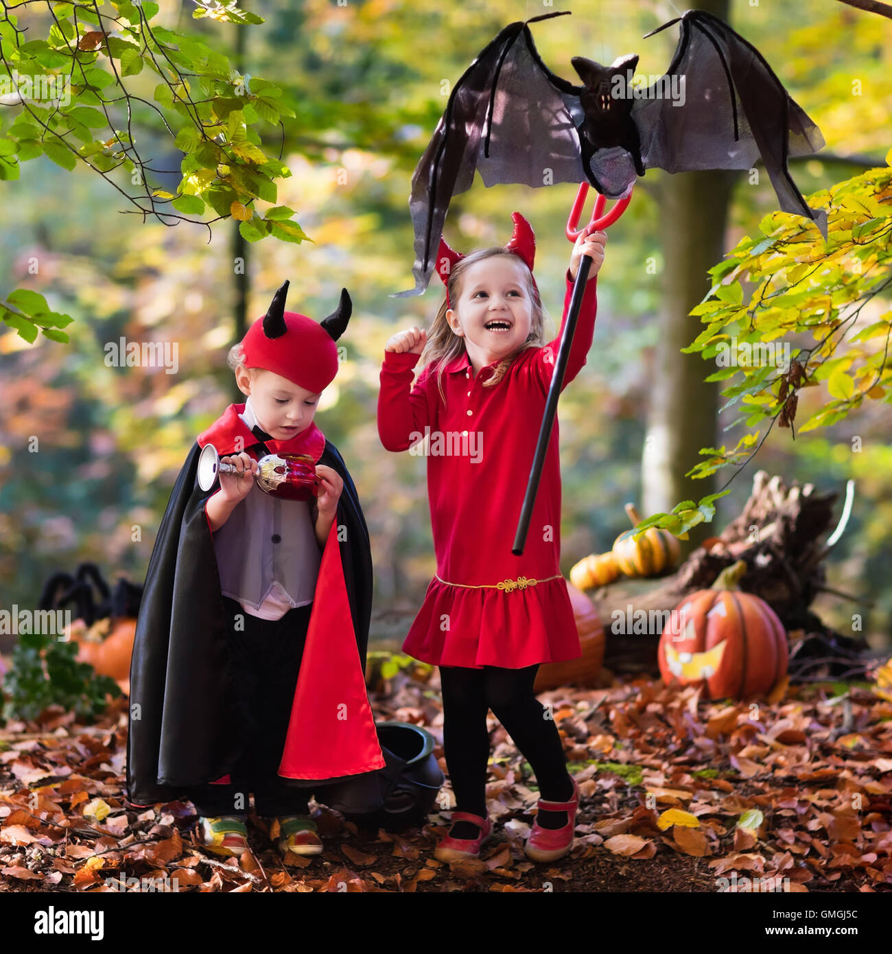 Funny Kids Halloween Costumes.Two Funny Kids Wearing Devil And Vampire Costume With Red