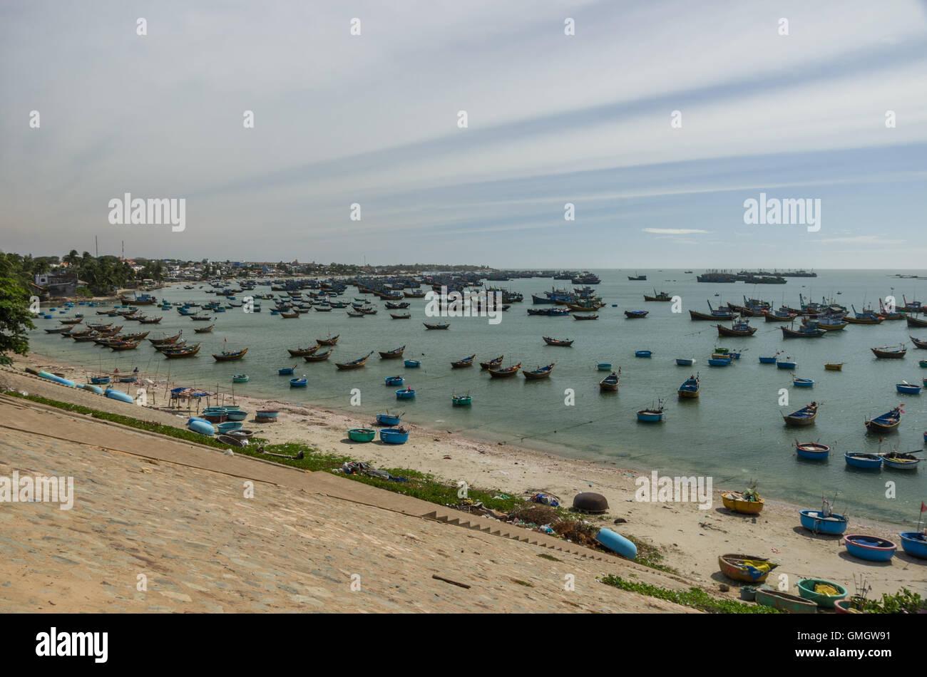 Fishing village and colorful fishing boats near Mui Ne at a sunny day. Vietnam - Stock Image