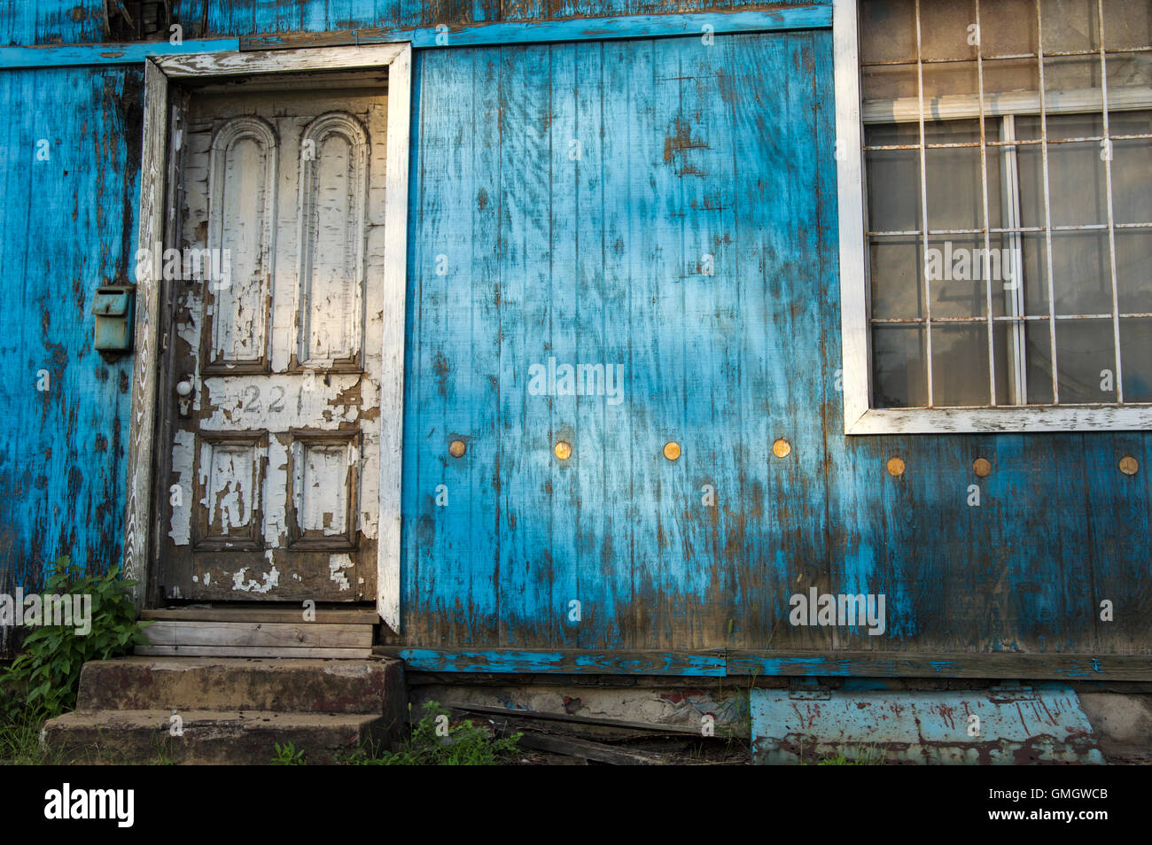 Golden dots on a wooden wall painted blue next to a doorway at a dilapidated house - Stock Image