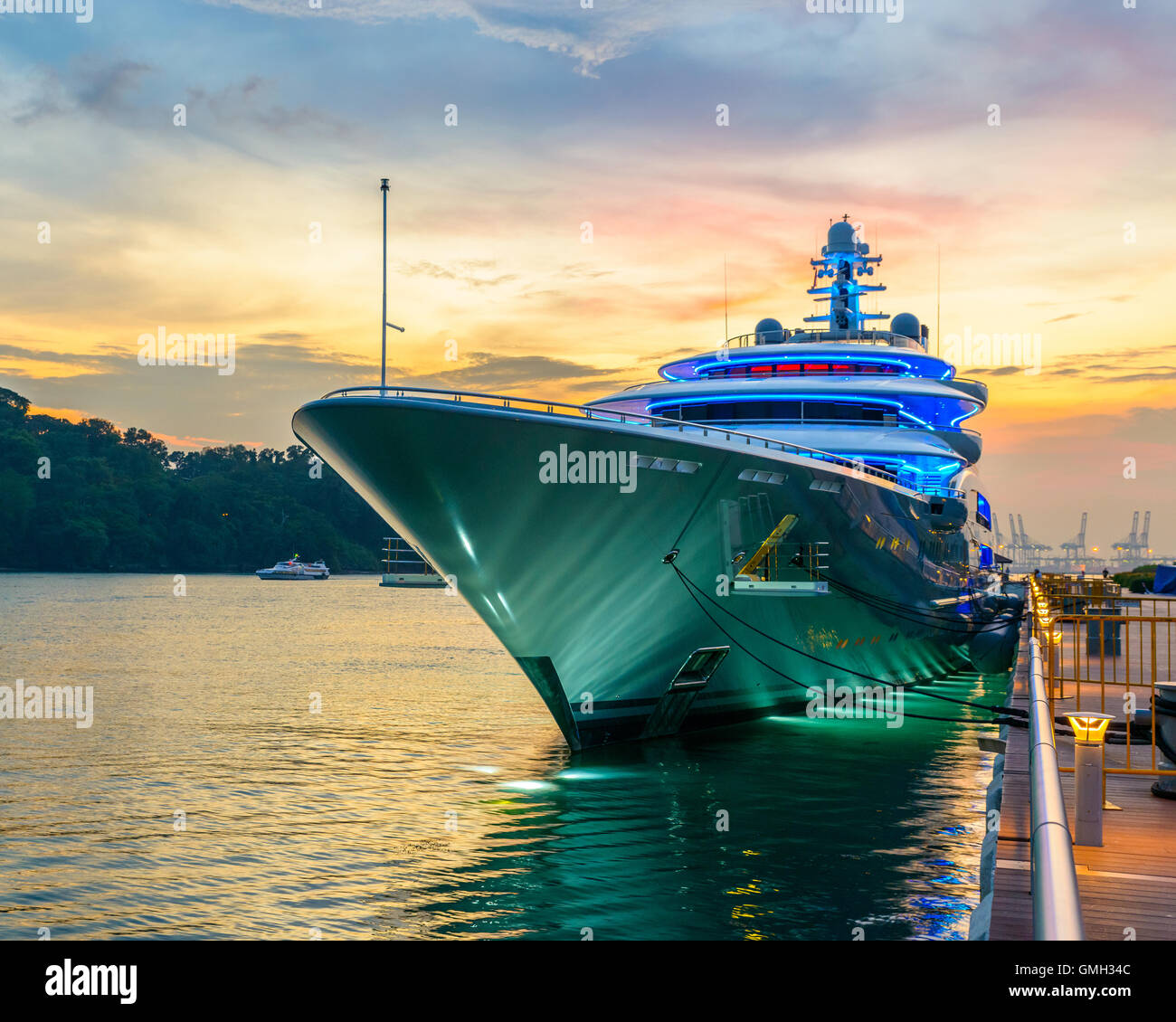 Docked green yacht at sunset in Singapore - Stock Image