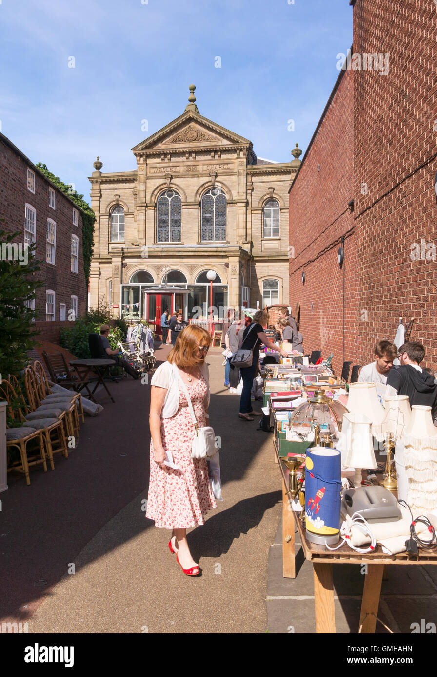 Woman looking at items for sale, jumble sale at the Wesley Chapel, Beverley, East Riding of Yorkshire, England, - Stock Image