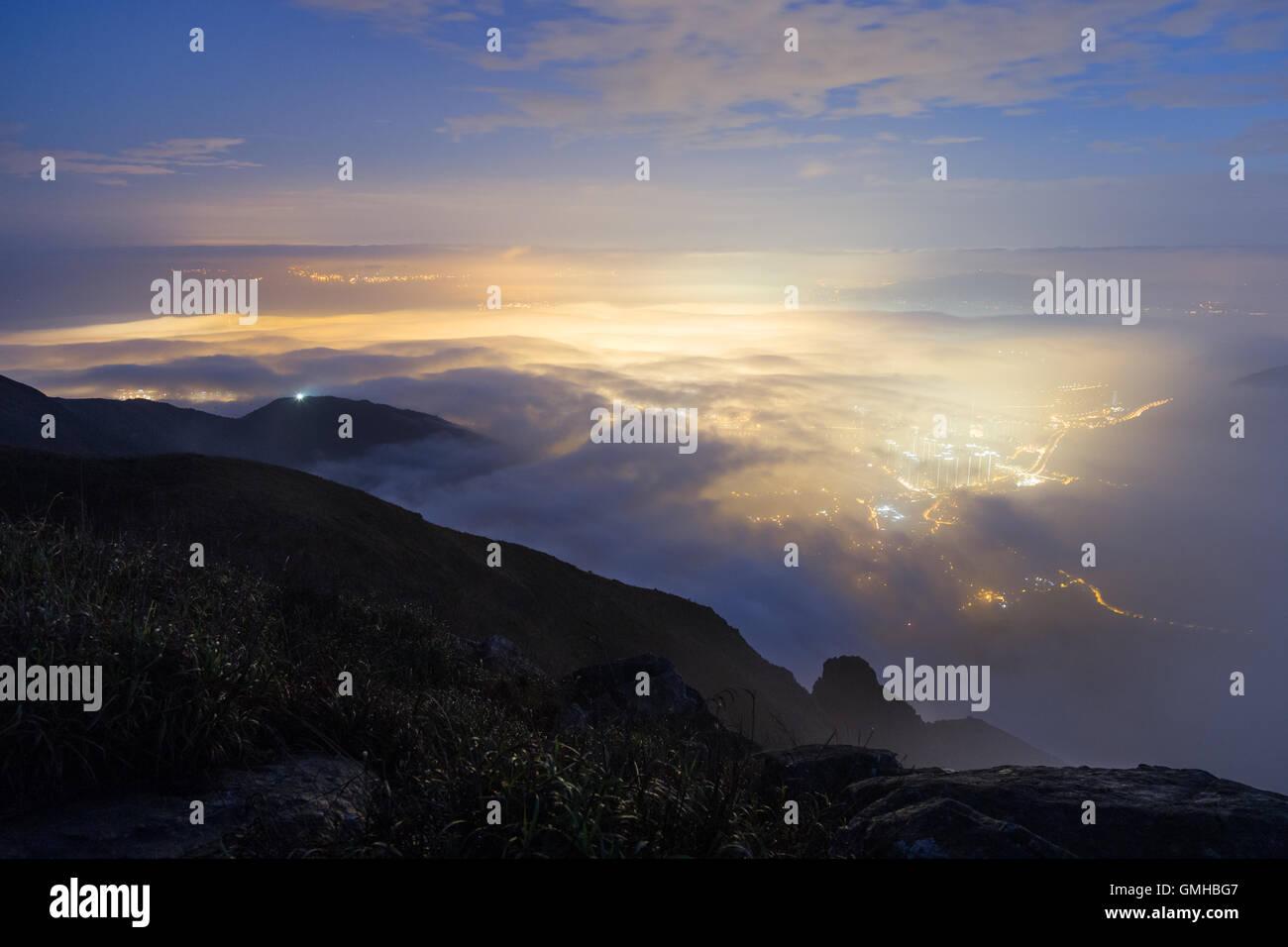 Lights of Tung Chung New Town below clouds on Lantau Island, viewed from the Lantau Peak in Hong Kong, China. - Stock Image