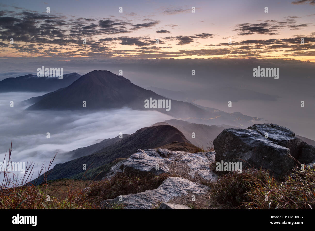 Clouds rolling over mountain on Lantau Island, viewed from the Lantau Peak (the 2nd highest peak in Hong Kong, China) - Stock Image