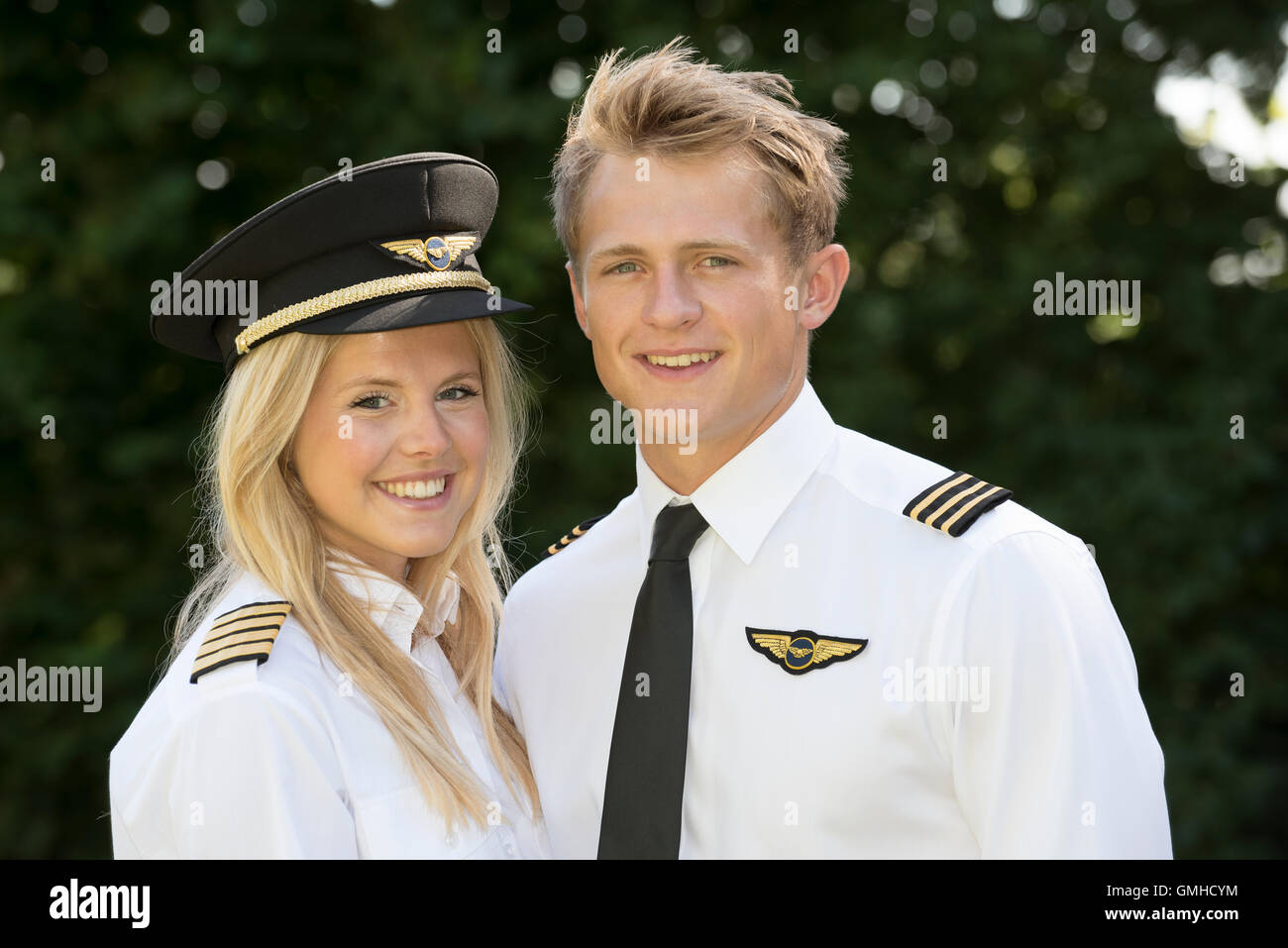 Portrait of two young male and female airline officers in uniform - Stock Image