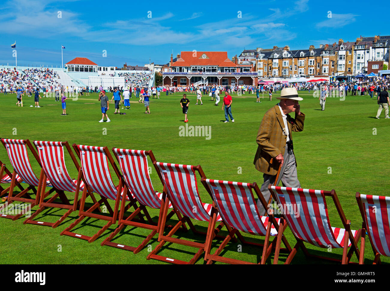 Old man walking past row of deckchairs during match, Scarborough Cricket Club, North Marine Road, Scarborough, North - Stock Image