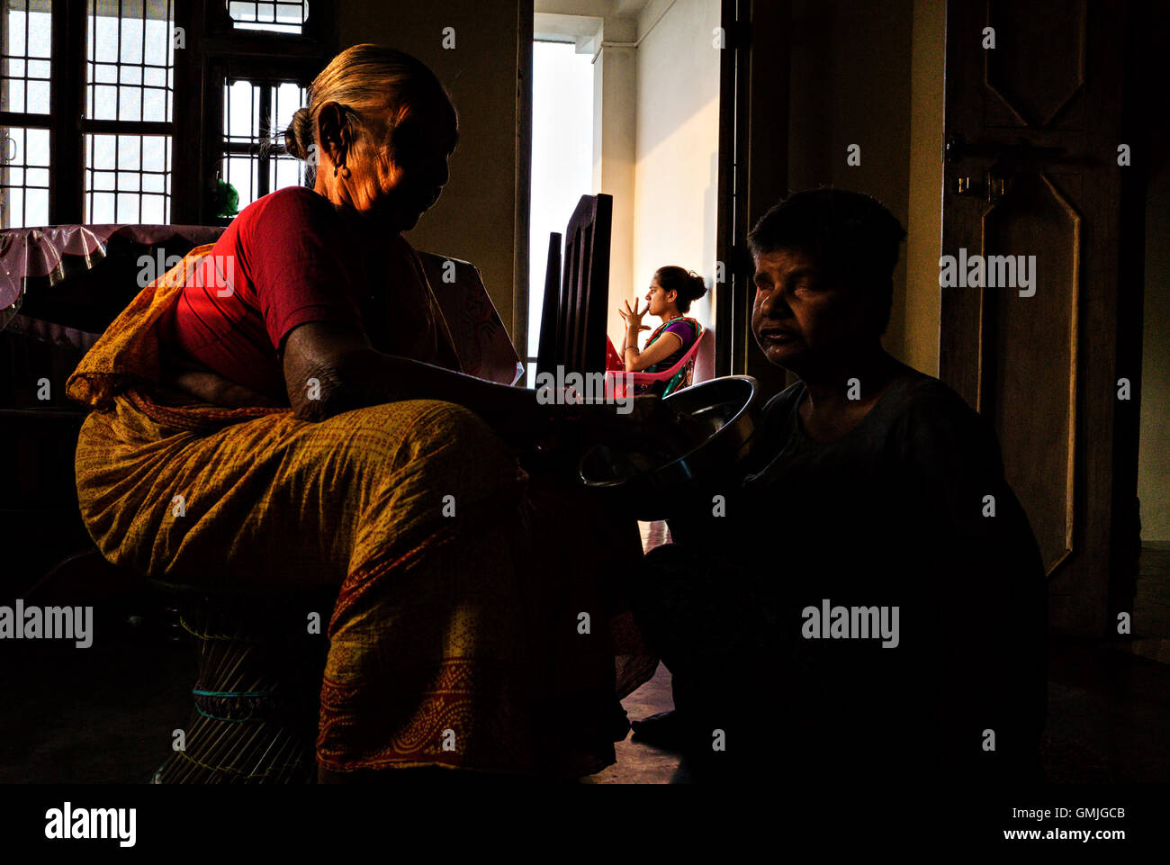 A mother hand feeding her physically and mentally challenged daughter - Stock Image